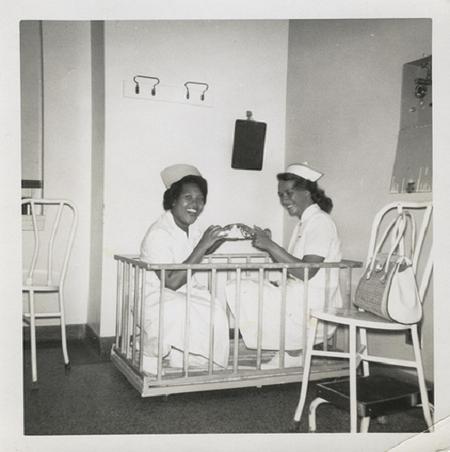 Happy nurses in a baby crib.