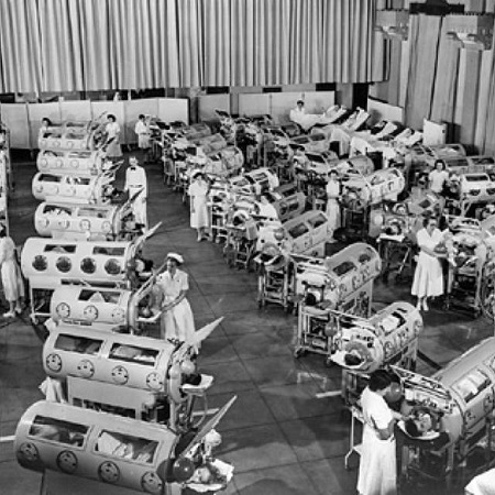 Nurses assisting patients with iron lungs.