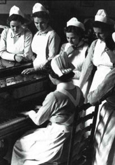 Nurses gather around a Piano, circa 1940