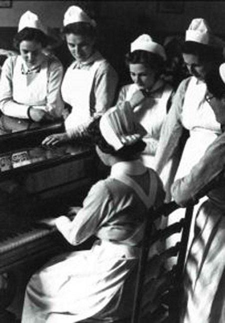 Nurses gather around a Piano, circa 1940