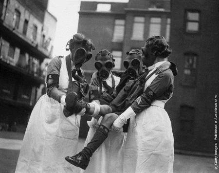 Vintage nurses wearing gas masks.