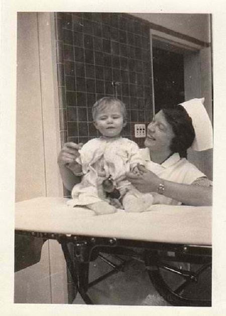 Vintage photo of a nurse with a baby, circa 1910s-20s.