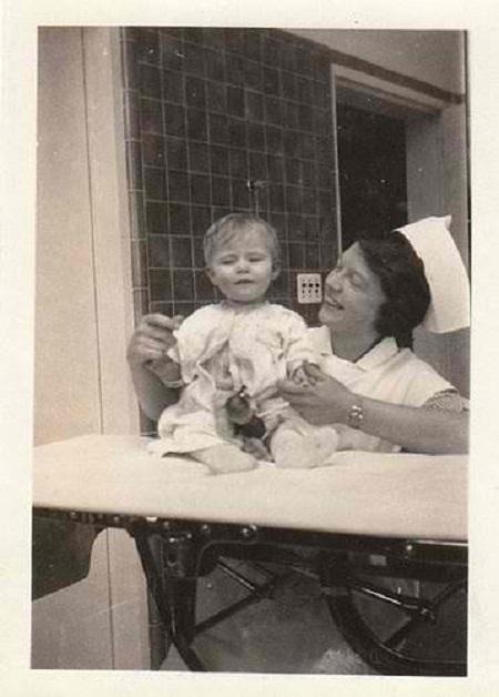 Vintage photo of a nurse with a baby, circa 1910s-20s.